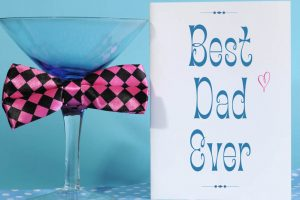 Happy Fathers Day, Best Dad Ever, greeting card with blue martini glass and fun pink check bow tie, on blue and polka dot background.
