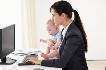 Working mother holding a baby while working on her computer
