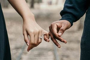 Man and woman holding pinky fingers together