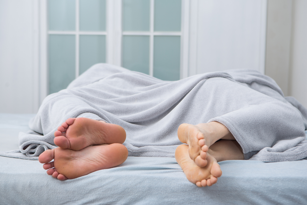 An Image of Couple sleeping apart to support an Article on Tips for Vasectomy Recovery